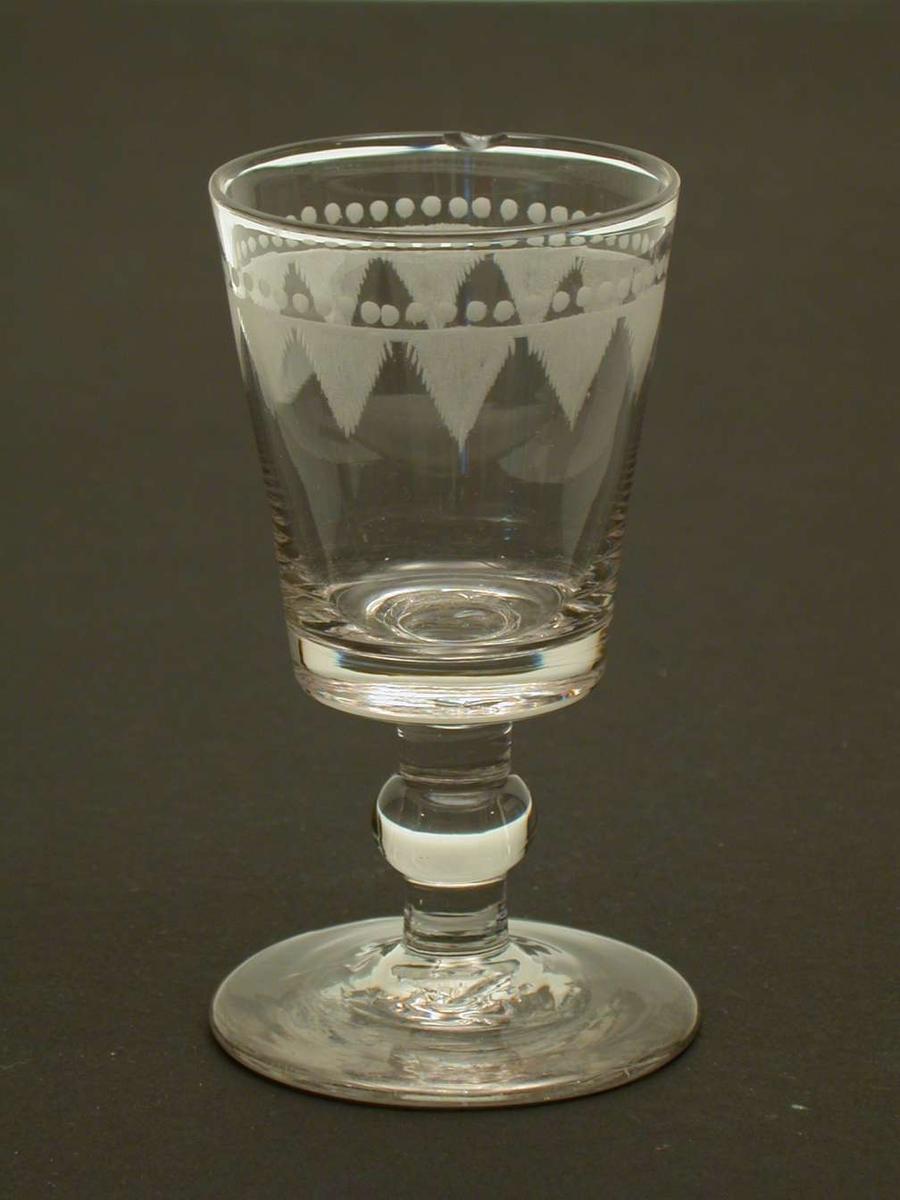 Dessertglass med kule på stetten og lambrequinmønster. Det er et hakk i randen på glasset.