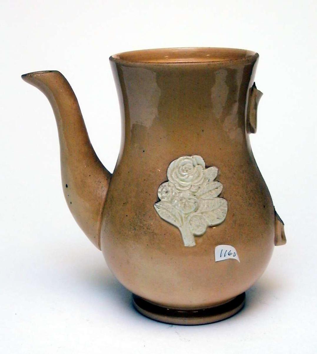Kaffekanne av gul keramikk med påsatt blomsterdekor. Dekoren er elfenbenshvit. Lokket og hanken mangler. Kannen har ingen produksjonsmerker.