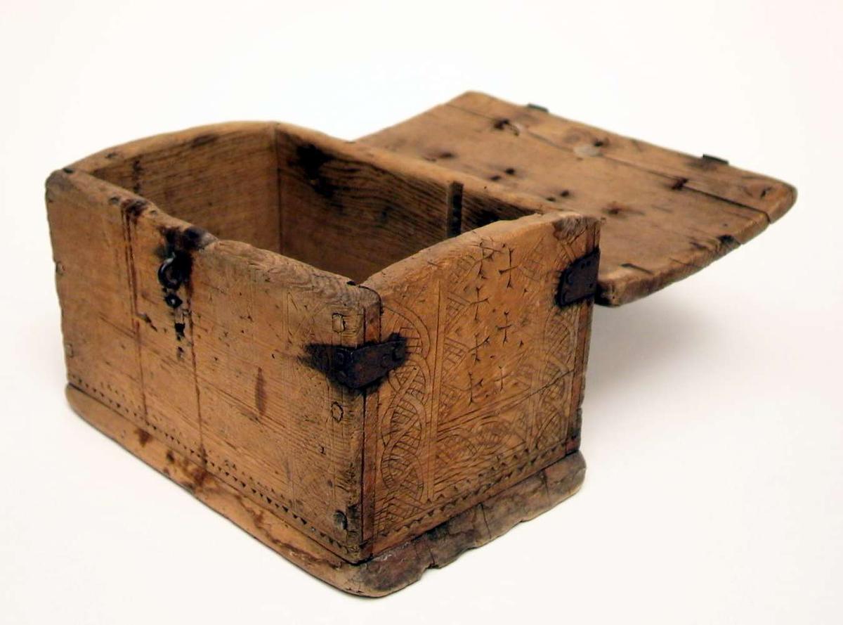 Skrin av tre og med beslag og hank av jern. Låsen er ikke komplett. Skrinet har utskjæringer. Treverket er sprukket og jernet er rustent.
