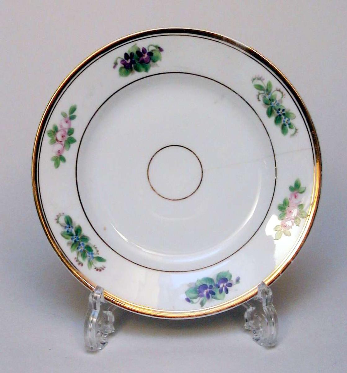 Asjett i hvit porselen med polykrom blomsterdekor og gullkant. Det er en sprekk i asjetten.