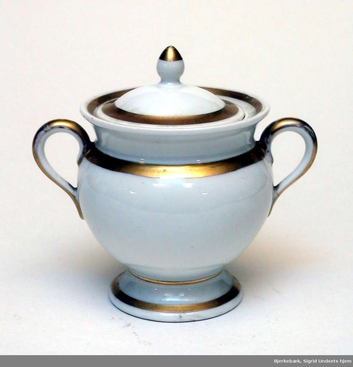 Sukkerkopp i hvit keramikk med forgylling. Den har lokk og to hanker. Fabrikkstempelet er Thomas, Bavaria.