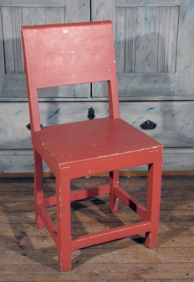 Rødmalt stol med tett rygg.