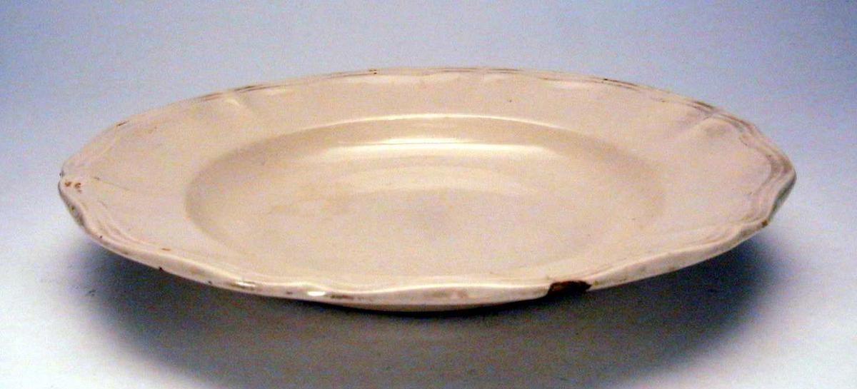 Elfenbensfarget, dyp tallerken. Den har rifler langs kanten.  Det er sprekk i tallerkenen. Glasuren er krakelert.