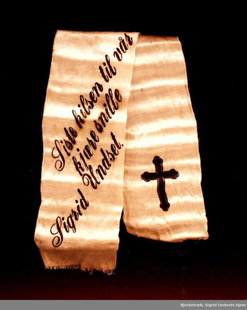 Bånd i hvit silke med sorte agramaner i den ene enden.. På båndet står det: Siste hilsen til vår kjære snille Sigrid Undset. I den andre enden er det et sort kors.