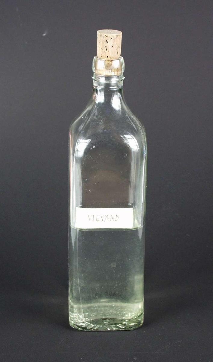 Whiskyflaske i klart glass, halvveis fyllt  med vievann.  Flasken har kork.