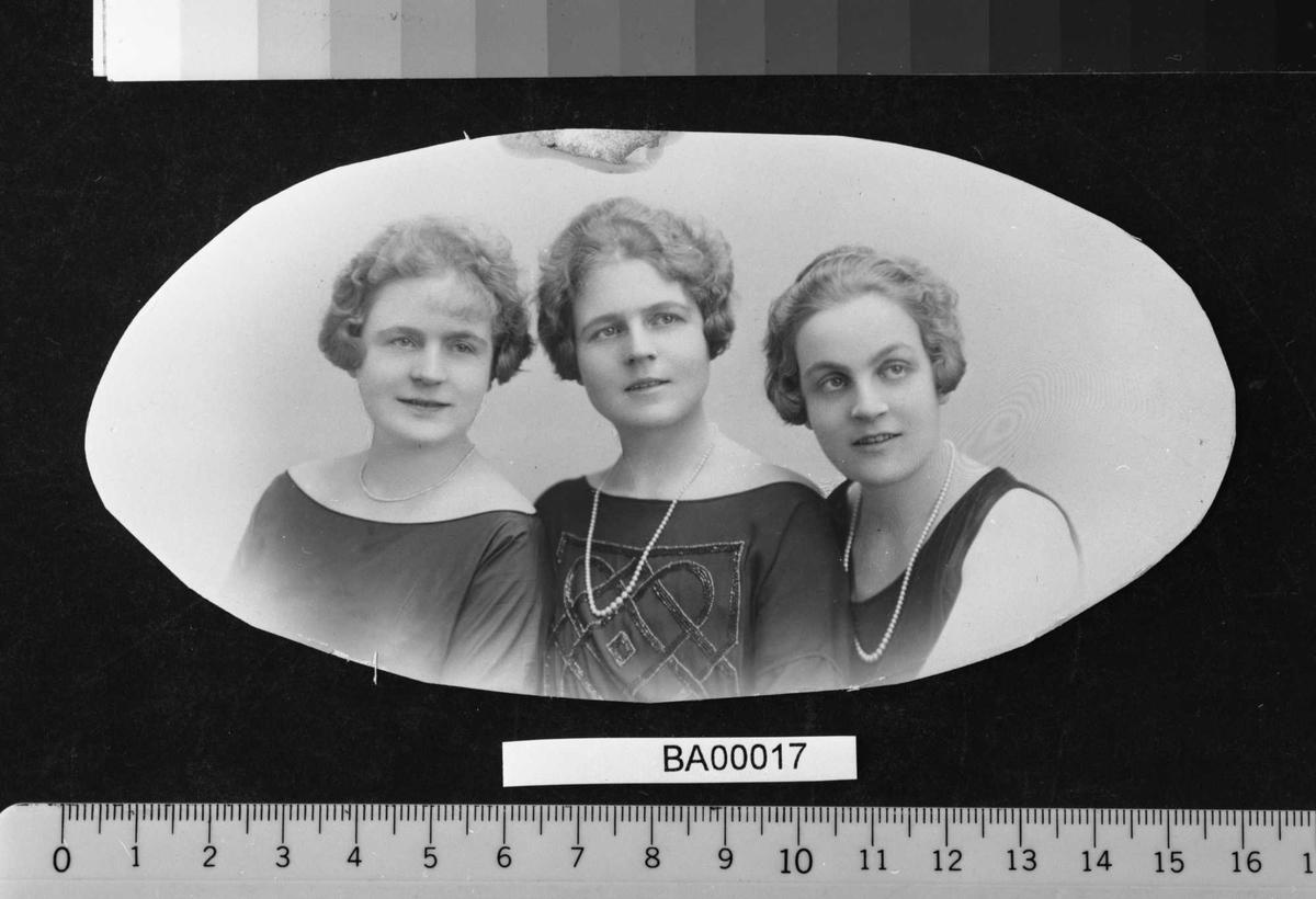 Atelierfotografi; familiebilde av tre unge damer i festkjoler, perlekjeder rundt halsen og fine korthårsfrisyrer lagt i bølger inn mot ansiktene. Brystbilde i oval bredde-ramme.