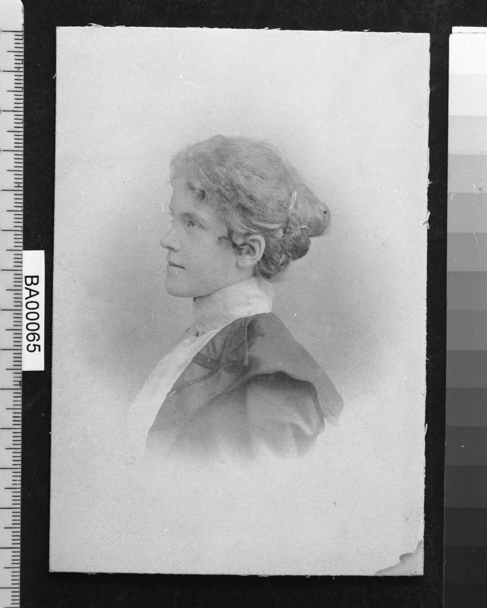 Portrettfotografi; en ung pike med oppsatt frisyre, ansiktet med alvorlig uttrykk, nesten i venstre halvprofil; kledd i høyhalset hvit bluse og mørk jakke med krave liggende ut over skuldrene.