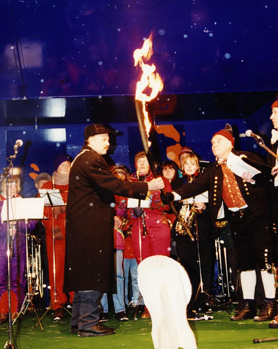 OL 1994, fakkelstafetten, Røros, ordføreren får overrakt fakkelen fra mann i bunad, de står på scenen, musikanter i bakgrunnen