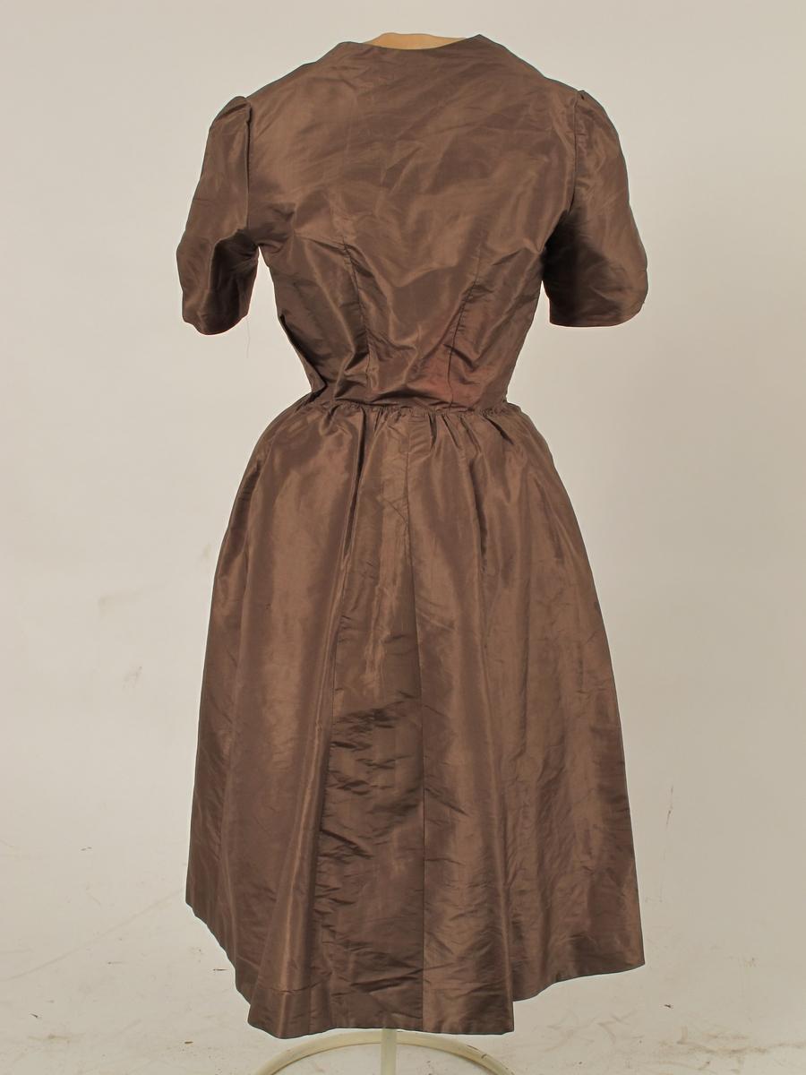 Omsydd kjole fra krigen 1940- 45,  Silketaft. mellombrun, med påsydde bånd i dypere brunfarge i ripsvevd silkemoiré.    Opprinelig gallakjole slutten av 1880 årene, muligens 1888. Nå delt i opprinnelig overdel og løse deler.