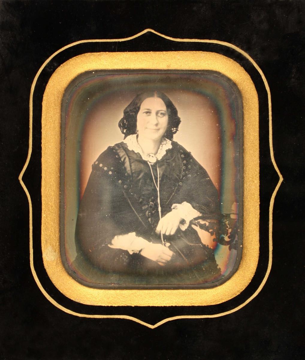 Portrett av Kaja Westergaard, 1856. Portrett av kvinne i en face, sittende, avsk. ved knærne, langt sort hår  med midtskill. Hvit blondekrave med brosje, holder med begge hender om en lang  lenke. Sort omramn. med gull inneramme.