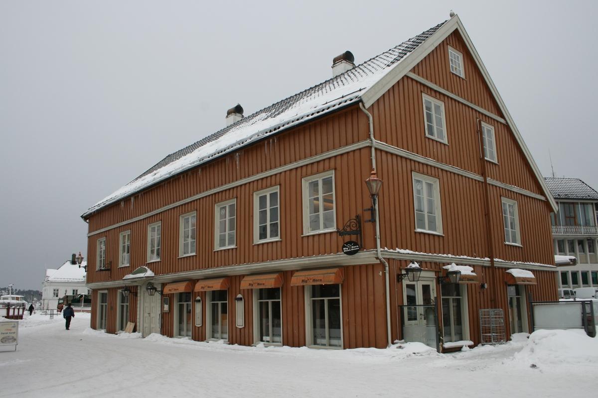 Det gamle politikammeret på Tyholmen. Snødekket bakke.