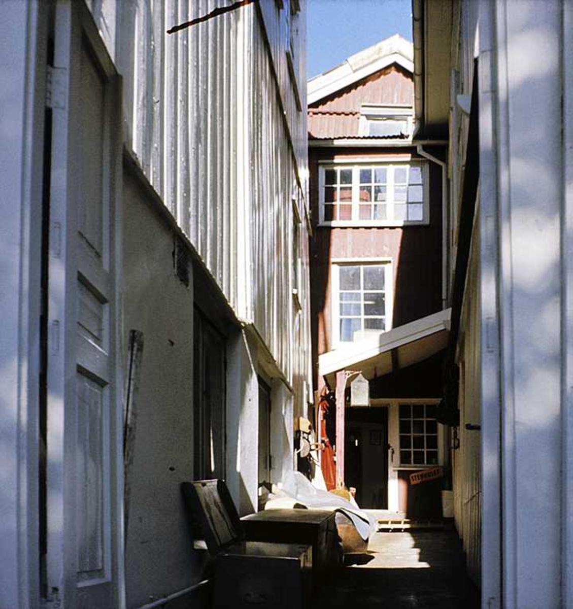 Smalt smau mellom bygninger, vegger panel, bygningsarbeid pågår.