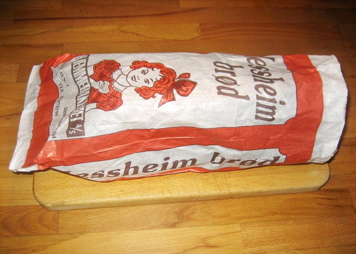 Forsiden: Tegning av en jente med sløjfe i håret og rutete kjole som spiser en brødskive. Tegningen er fargelagt i rødt, hvit og sort.