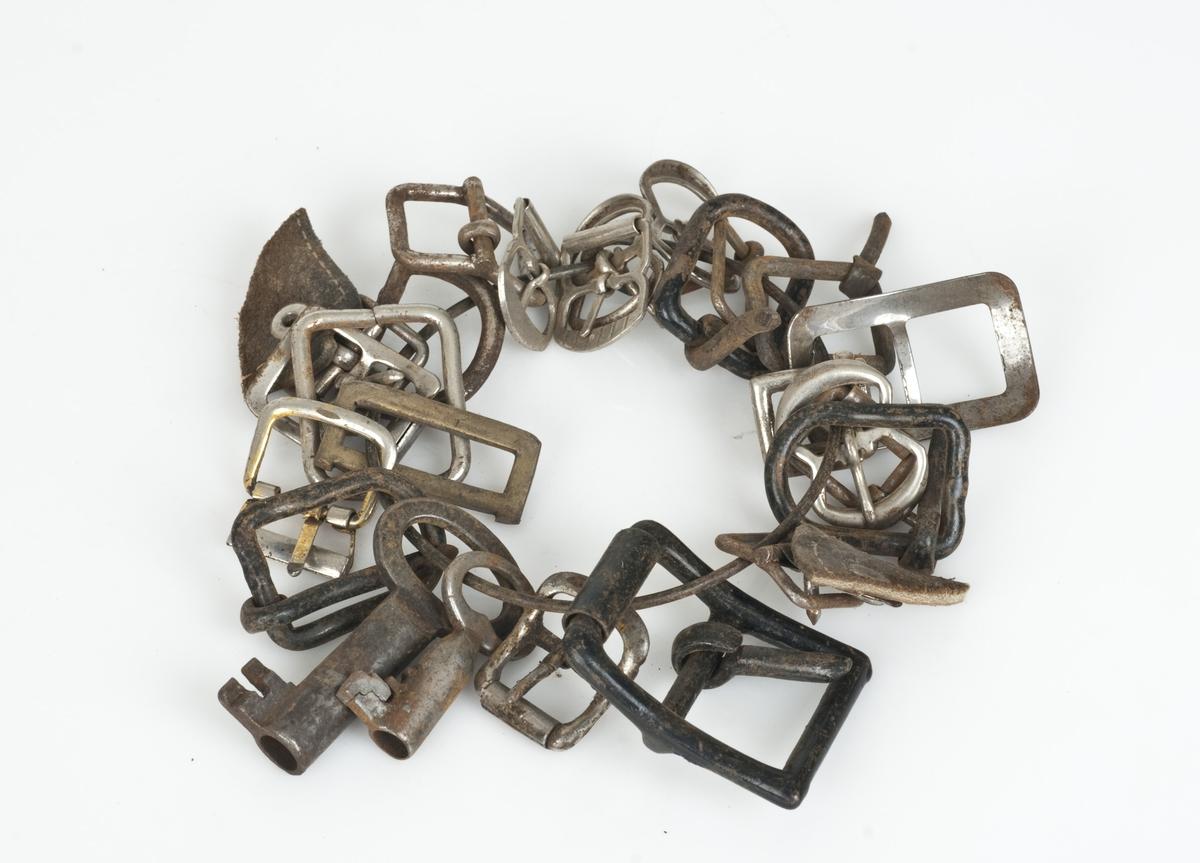 23 beltespenner og to nøkler bundet sammen med ståltråd.