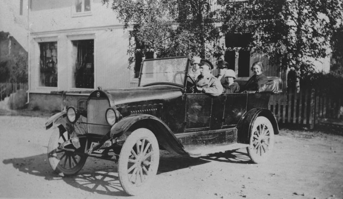 6 personer i bil utenfor kjøpm. Weydahl, Kråkstad sentrum. - Akershusbasen / DigitaltMuseum