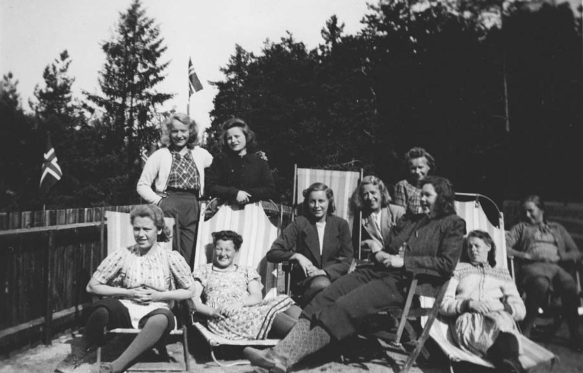 Gruppebilde. Damer sitter i hagestoler.