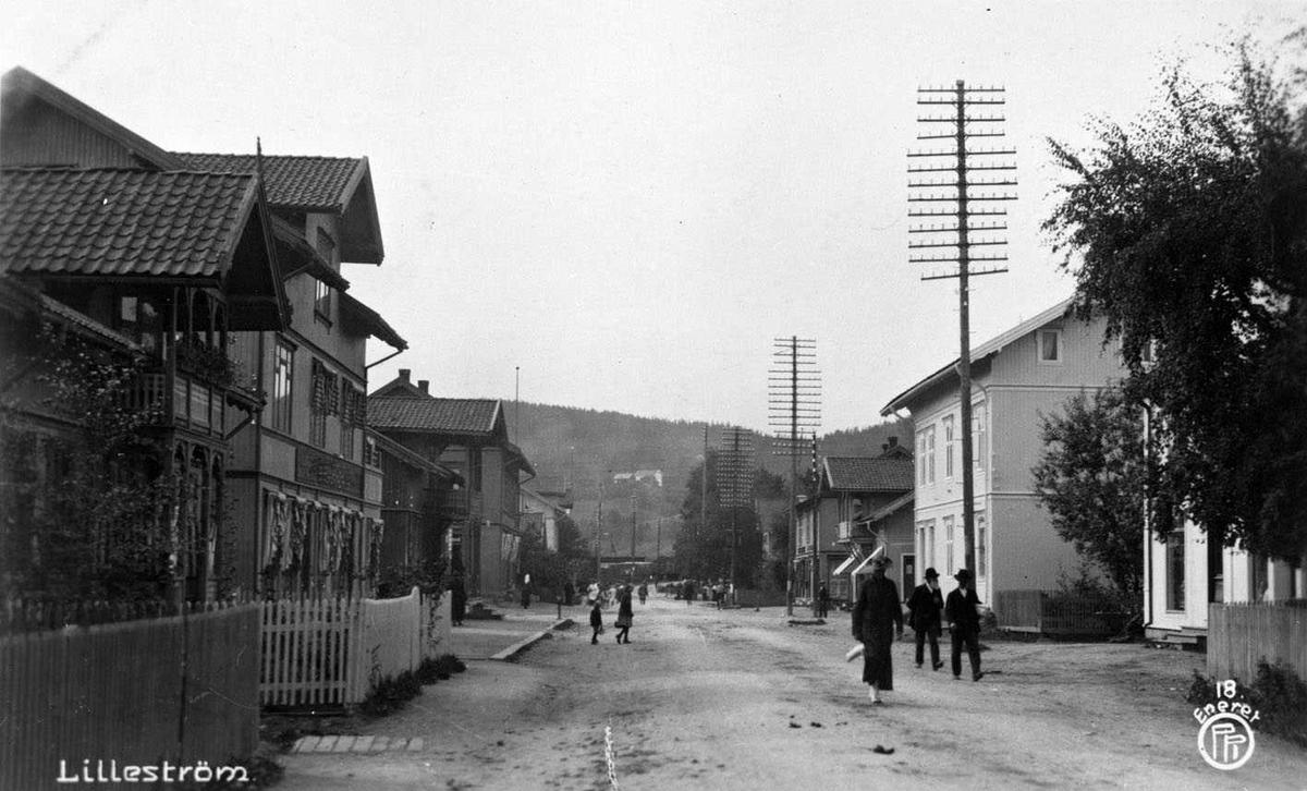 Lillestrøm  Storgaten nedre del med Lillestrøm stasjon i bakgrunnen. På høyre side går en rekke telefonstolper. Postkortfoto: 18 Eneret P?