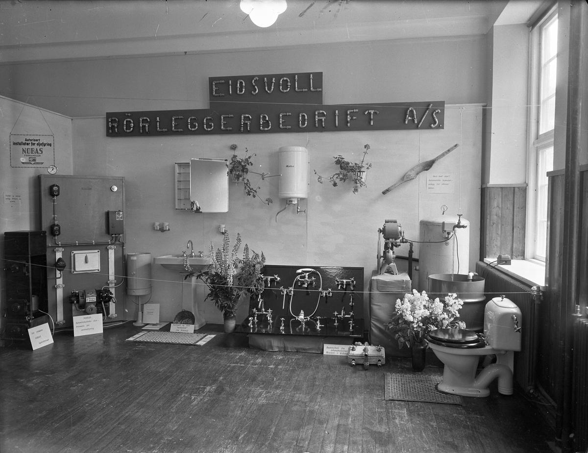 Fra Eidsvoll Bygdeutstilling i 1955.  Stand fra Eidsvoll Rørleggerbedrift AS. Dusjbatterier, toalett, varmtvannstanker, kaminbrenner, oljebrenner/sentralfyrkjele m.m..