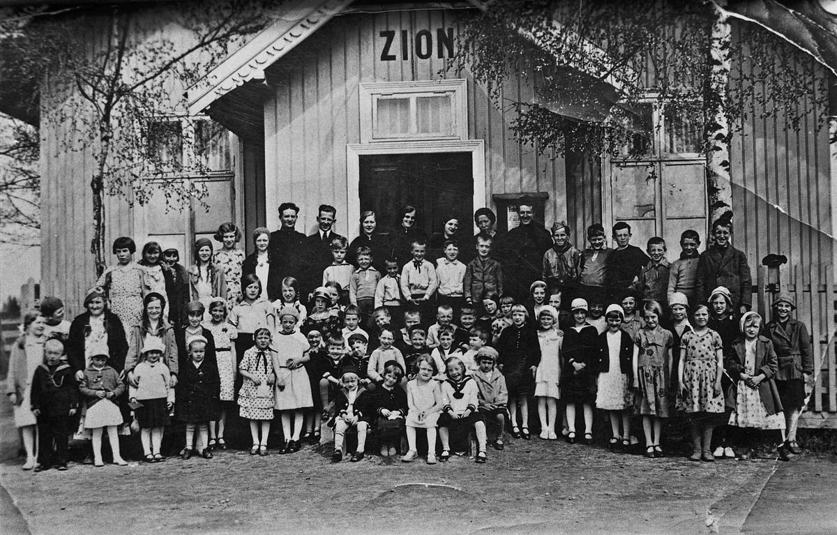 Barn og voksne utenfor menighetshuset ZION.