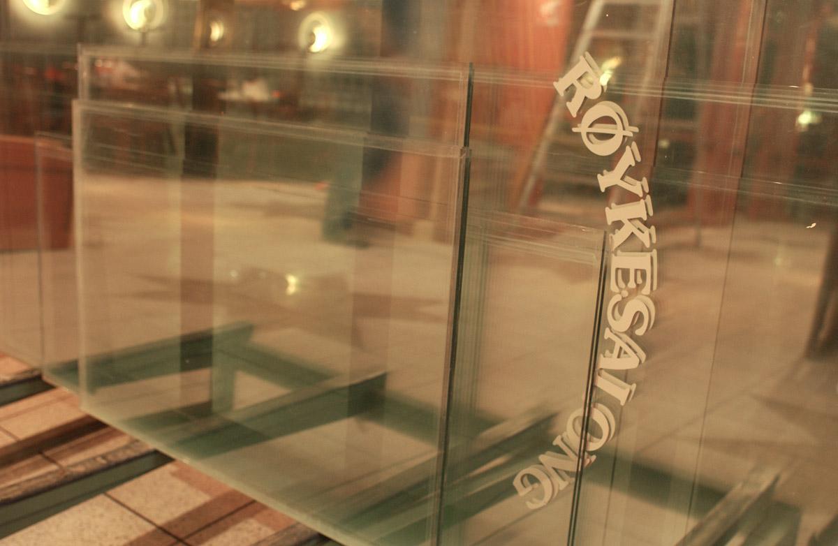 """Nedmontering av røykerommet. Glassdør lagt horisontalt. Påskrift: """"Røykesalong"""" Vinterbro senter, OBS! kafe."""