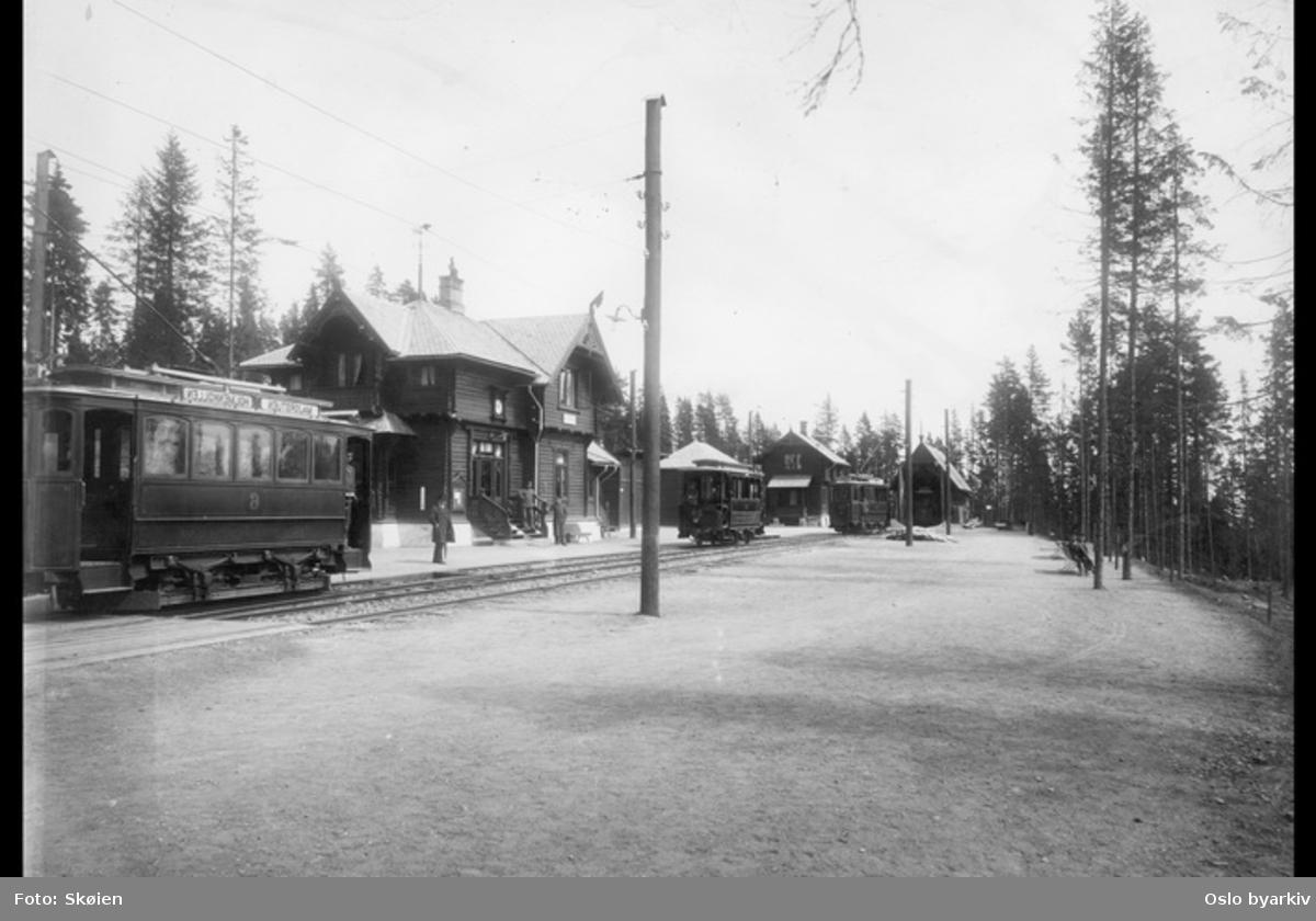 Tre sporvogner på Holmenkollen stasjon. Stasjonsanlegg i sveitserstil; vognhall, godshus og utedo. Godshuset er nå stasjonsbygning på Lillevand stasjon