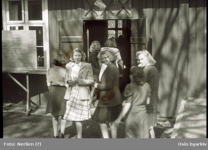 Undervisning i provisoriske lokaler ved Sagene skole under okkupasjonen. Inn etter friminutt. Jenter (fra venstre Randi Fjeld, Eva Nilsen og Marit Johansen) utenfor undervisningslokalet i Biermannsgården i Maridalsveien.