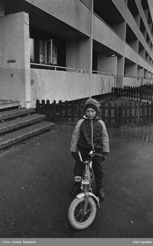 Gutt med sykkel foran boligblokk. Fotografiet er fra prosjektet og boka ''Oslo-bilder. En fotografisk dokumentasjon av bo og leveforhold i 1981 - 82''. Kontakt Samfoto ved ev. bestilling av kopier.