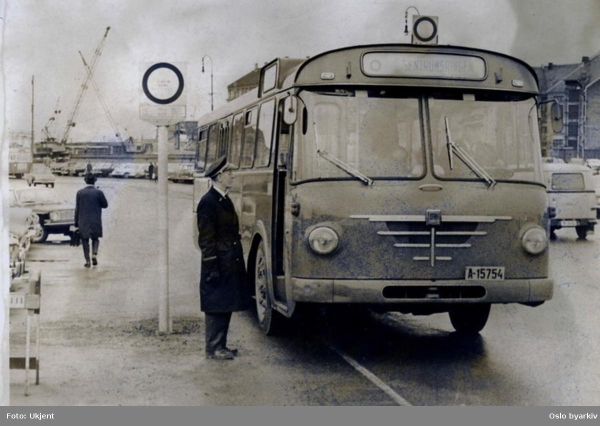 """En Büssing Senator, eller """"pinnevogn"""" som den ble kalt pga. den bitte lille girspaken, ved endeholdeplass for Sentrumsringen på Grønlands torg. Sentrumsringen ble opprettet da T-banen åpnet 12/9-66 som en slags matebuss til T-banen i sentrum. Linja var ingen suksess og ble lagt ned 17/6-67. Fotografi publisert i Dagbladet, den 30. mars 1967."""