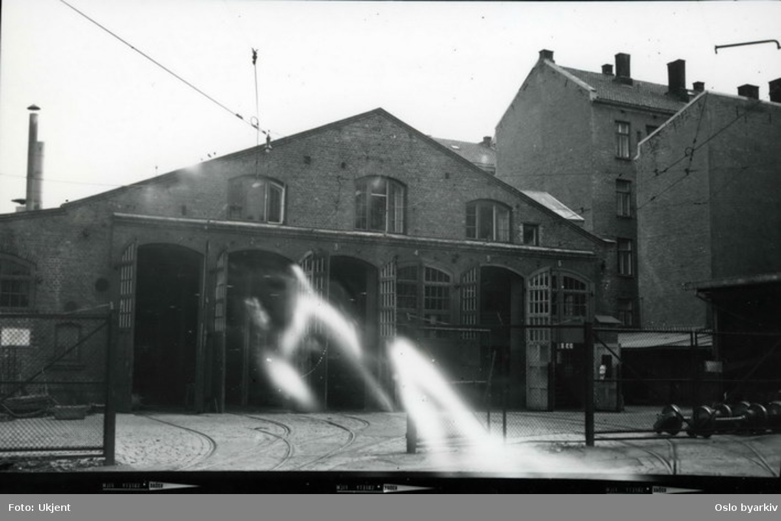 Oslo Sporveiers første hovedkvarter. Hestestallen og trikkehallen på Homansbyen i Sporveisgata 8 (kalt Homansbyen verksted). Driftsområde for Kristiania Sporveisselskab. Staller og vognhall (med smie og vektbod). Ombygget 1899 fra stallbygning til trikkestall (p.g.a. elektrifiseringen). Virksomheten opphørte 1966. Revet 1969. Bildet fra første halvdel av 1960-tallet.