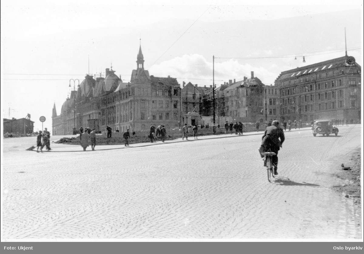 Mann syklende opp en brosteinbelagt Henrik Ibsens gate (Drammensveien). Opparbeidelse av 7. Juni plassen til Blomster/grøntanlegg. Victoria terrasse med Glitnegården til høyre. Mellom ses ruinene av bygården til Bondeungdomslaget (bombet 1944).