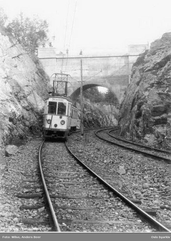 Bærumsbanens motorvogn type A (i Jarskjæringa på Lilleakerbanen / Bærumsbanen) under brua som fører Vollsveien over banen og Bærumsveien. Bildet tatt 1. juli 1924, da linjen ble åpnet til Bekkestua.