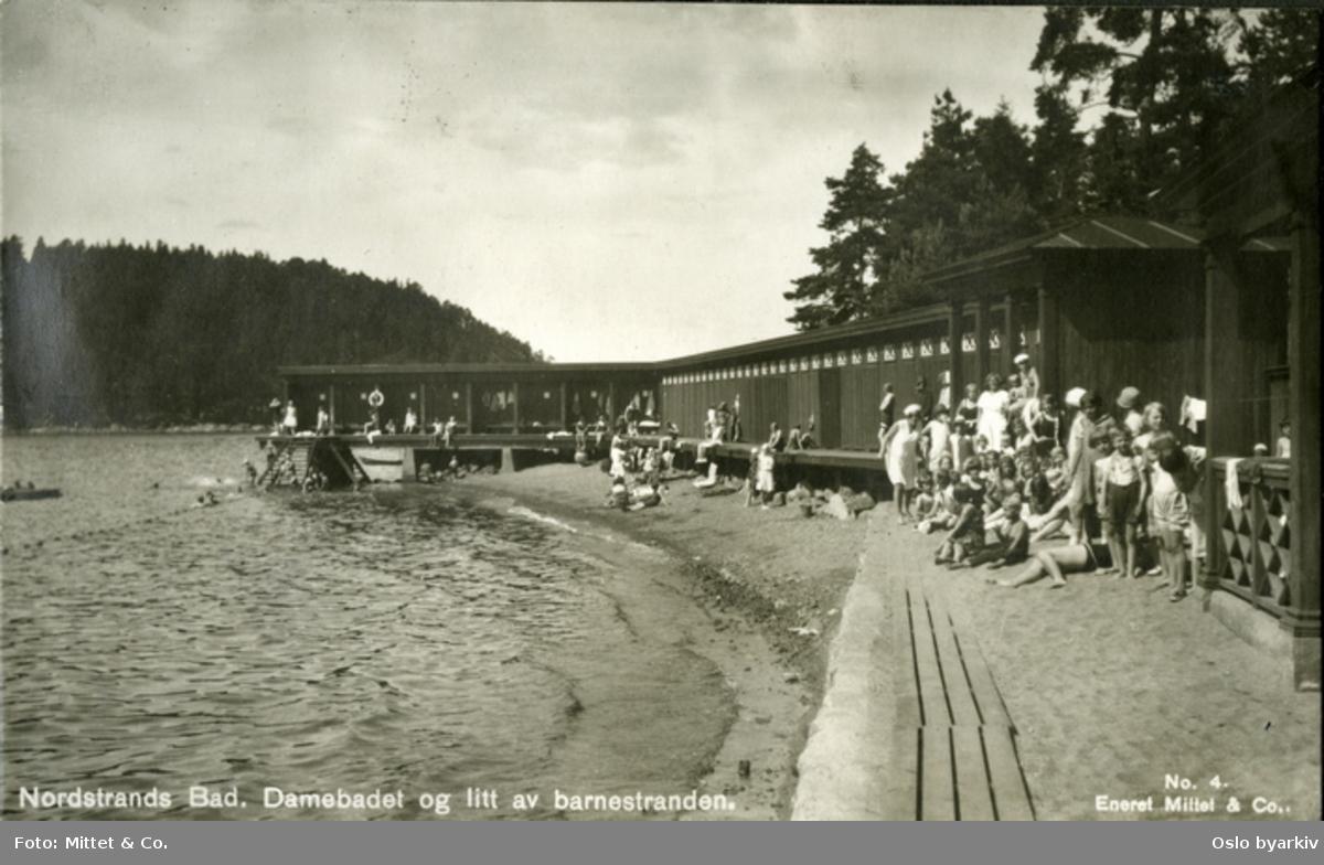 Skiftekabiner. Sandstrand. Kvinner, barn og badebetjening. I bakgrunnen ses Ulvøya. Postkort No.4. Eneret Mittet & Co.