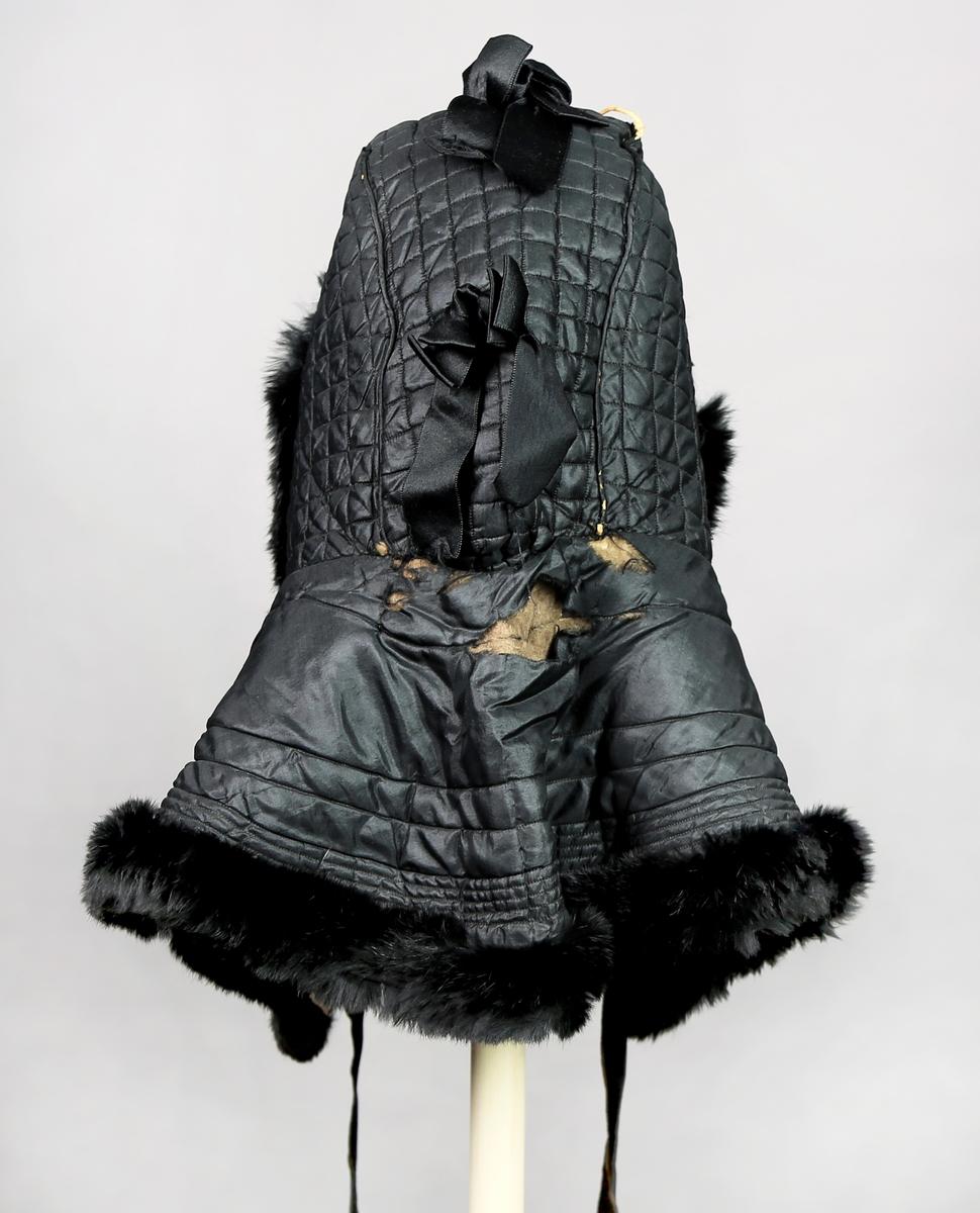 Hette med skulderlang kappe og knytebånd. Av maskinvattert silke. Det er sløyfe både foran og bak, og en rosett. Nede er det pelskant