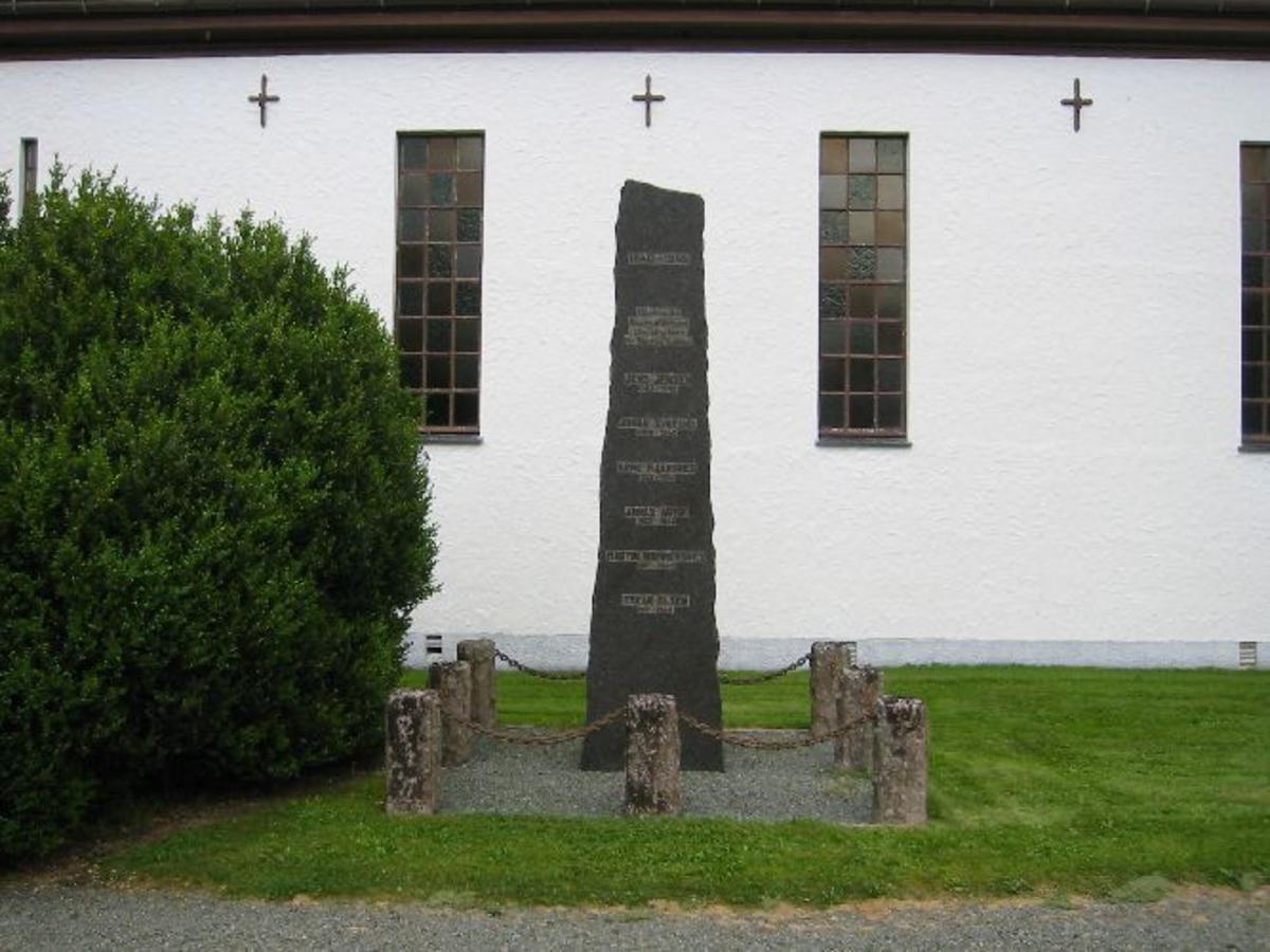 Bauta i granitt med polert fremside med inskr. H 2,25 b 0,70 d 0,25 som står på singellagt område med 8 steinsøyler med kjetting mellom 2,50 x 2,50