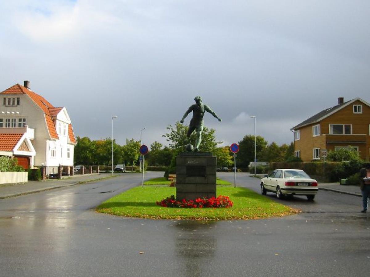 Statue av en fotballspiller på sokkel,statuen er 2,2 m. høy og av bronse. Sokkel 1,80 m høy Bredd1,45 m D 1, 45 m. Påmontert en bronseplate med inskripsjon.