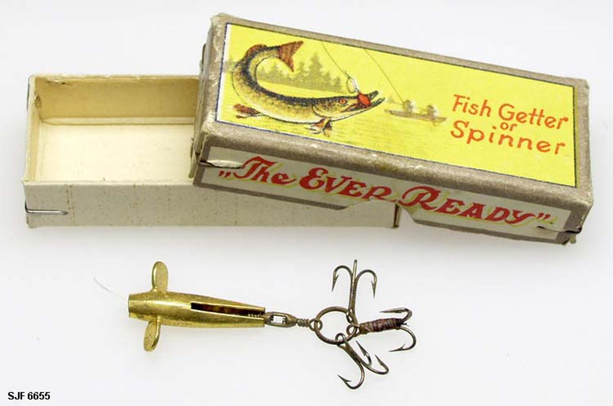 """Devonsluk med form som en fisk, ensfarget """"gullfarge"""".  """"Vinger"""" bak hodet.  3 kroksett med 3 kroker i hvert, ett under buken, ett på ryggen og ett bakover fra halen.  Sluken har en sene som er 3 cm lang. Sluken er oppbevart i en liten eske med gult merke på lokket. Engelsk tekst. Form: Fiske-form"""