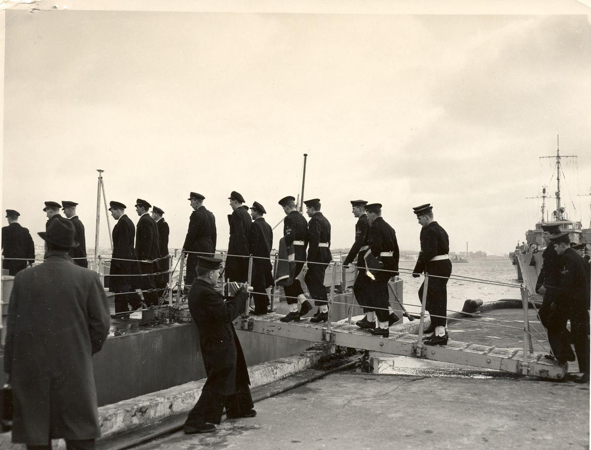 """Overtakelsen av River-kl.fregatt KNM """"Draug"""", ex. HMCS Pentang. Ombordstigning.Jager av Cresent-klasse, innkjøpt fra Storbritania i 1946. Fikk norsk kommando heist i Chatham 10. oktober samme år. Etter utprøving ankom jageren Horten 21.desember 1946. Ble adoptert av Stavanger by 16.mai 1947. Var i 1948 utsatt for et alvorlig uhell da dokkputene sviktet under doksetting i Stavanger og bunnen ble slått mot bunnen av dokken og påført store skader.  Stavanger gjorde tjeneste frem til 1966 da det ble utrangert. Ble benyttet som målfartøy før den i 1972 ble solgt og slept til Belgia for hugging."""