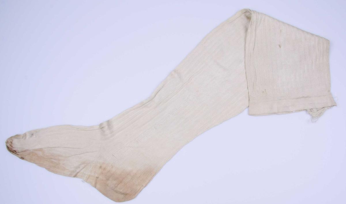 Hvit silketrikot, stripet (finere og grovere masker) med glatt tå og glatt kant oppe. De har søm bak, under foten og tversover ved tåen. Brodert pil.