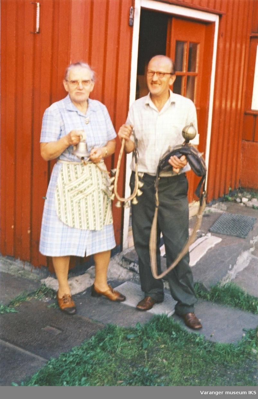 Ida og Alf Tuomainen viser framfor hesteutstyr utenfor Tuomainengården. Ca 1970-tallet