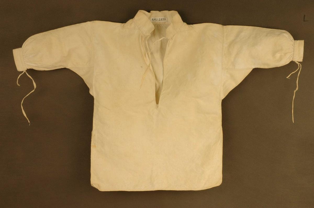 585968d1 Bomullskjorte til barn. Bryståpning med liten pyntesøm i enden av åpningen.  Liten ståkrage og