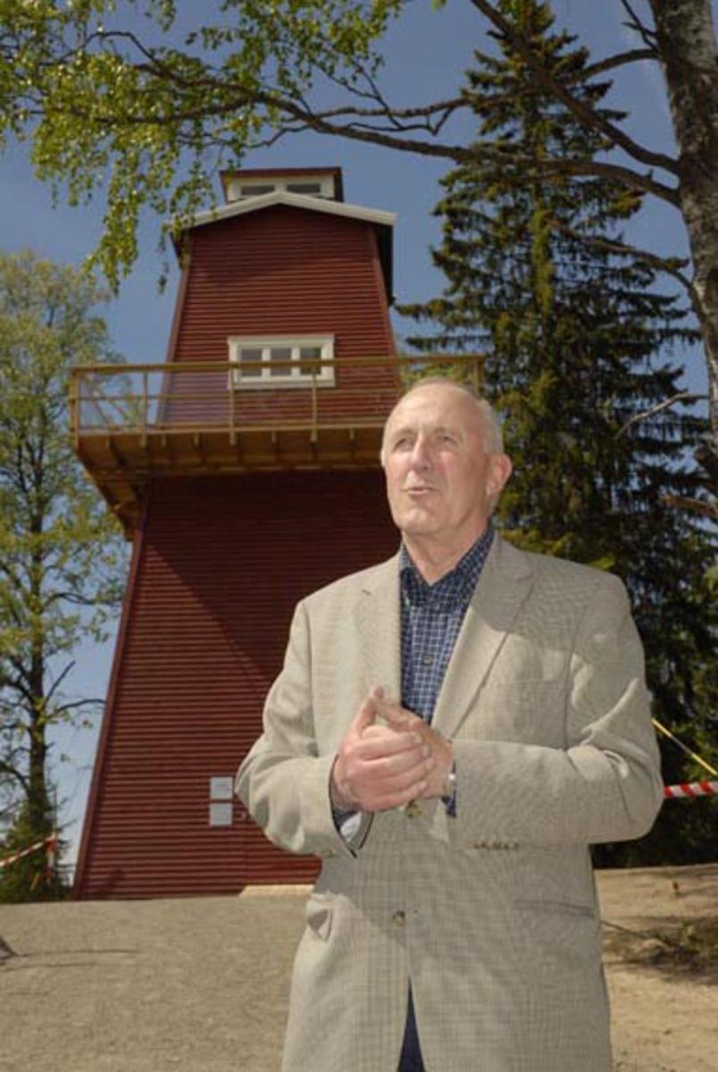 Norsk Skogmuseums direktør i perioden 1994-2006, Yngve Astrup, holder tale under åpningen av en kopi av brannvakttårnet på Haukenesfjellet i Rømskog i forbindelse med representantskapsmøtet på Norsk Skogmuseum 28. mai 2008.  Astrup var leder for museet da den første befaringa på Haukenesfjellet fant sted (2001), og det var i hans ledertid at forsikringsselskapet Skogbrand bevilget 800 000 kroner til en kopi av tårnet på museets område.  Astrup er fotografert med brannvakttårnet i bakgrunnen.   Brannvakttårnkopien på Norsk Skogmuseum ble reist i samarbeid mellom museets vaktmestere og entreprenørselskapet Mesterbygg Hedmark vinteren 2007-2008. Prosjektet lot seg realisere takket være sponsormidler fra forsikringssekskapet Skogbrand, materialtilskudd fra Moelven-konsernet og gratis maling og beis fra Jotun-fabrikken.  Det originale tårnet ble bygd i 1953 og var i drift som brannovervåkingssted fram til 1976.  Seinere har det i en viss utstrekning vært brukt som kvilested for turgåere i området.  Etter at museet begynte å bygge sin kopi av anlegget innledet lokalmiljøet i Rømskog et samarbeid med Turistforeningen (DNT Indre Østfold) om restaurering og ominnredning med sikte på at tårnet skal kunne brukes som overnattingssted for brukere av «Grensestien».    Kopien på Norsk Skogmuseum ble innredet med en utstilling om skogbrann og skogbrannvern i tårnfoten og et vaktrom anno tidlig 1970-tall samt et peilerom med kartbord øverst, 11-12 meter over bakken.