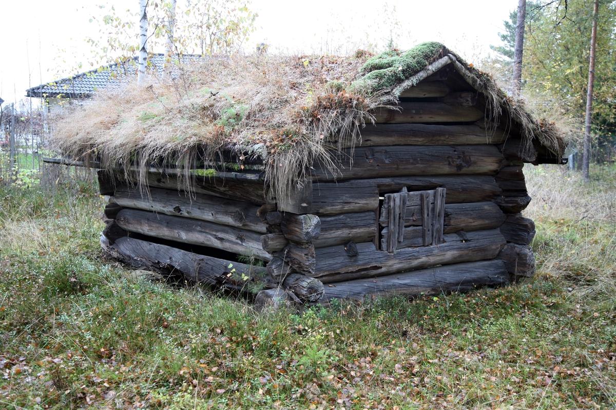 Løe av laftet tømmer med dør i gavlen