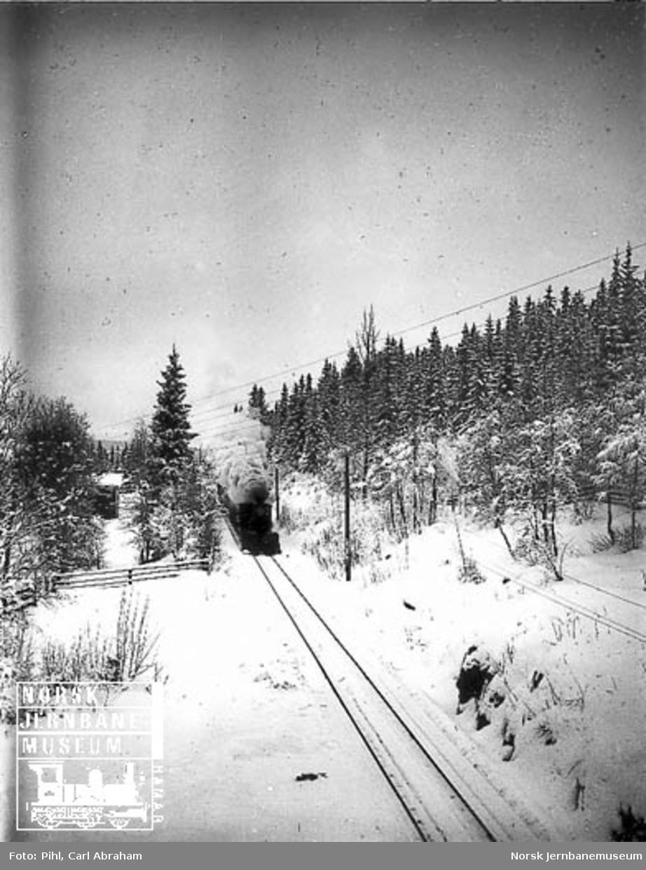 Vinterbilde med damplokomotiv type XVII med stor frontplog foran toget