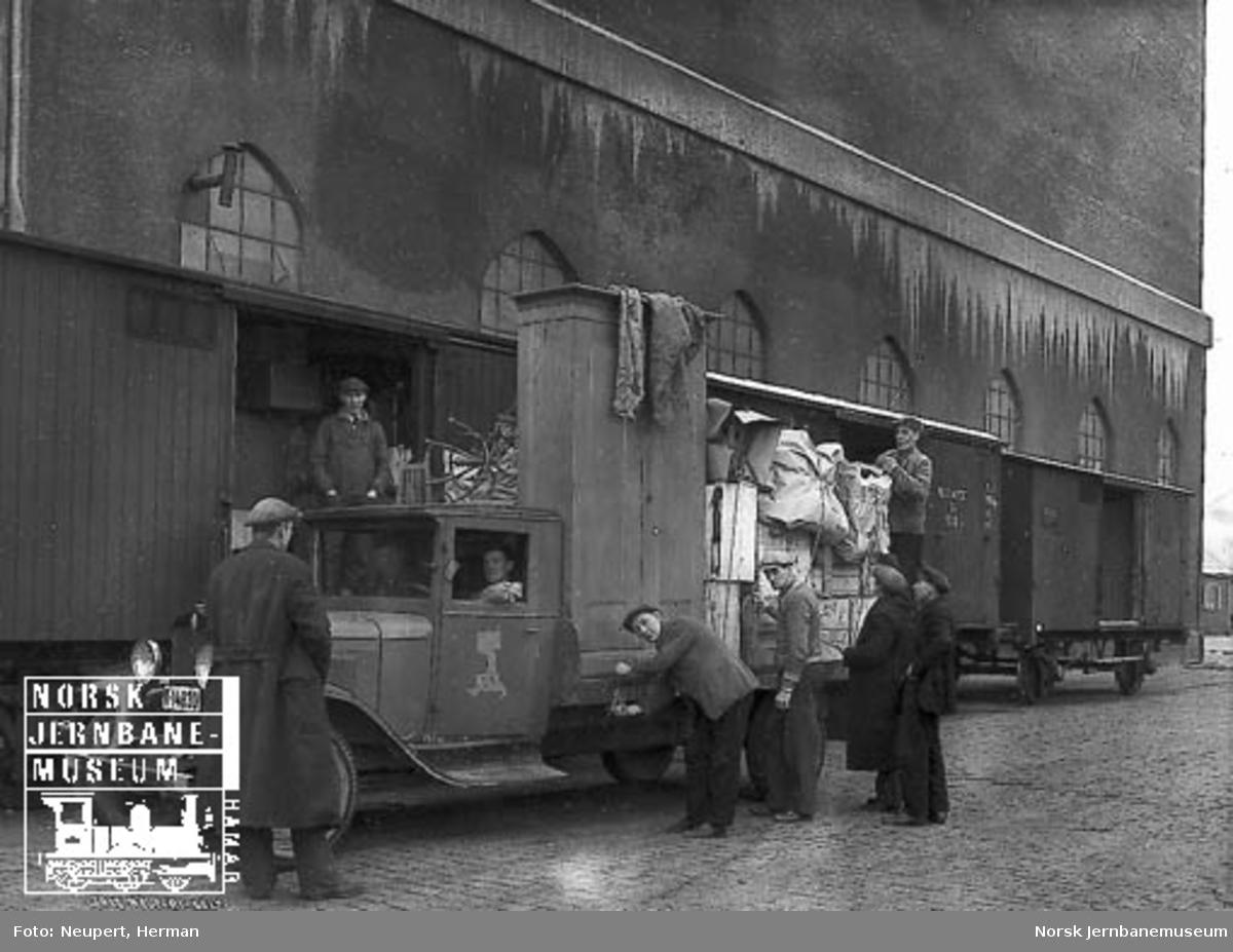 """Gods fra en godsvogn blir lastet over på lastebil fra """"Visergutt & Transportbyraaet Kjapp"""""""