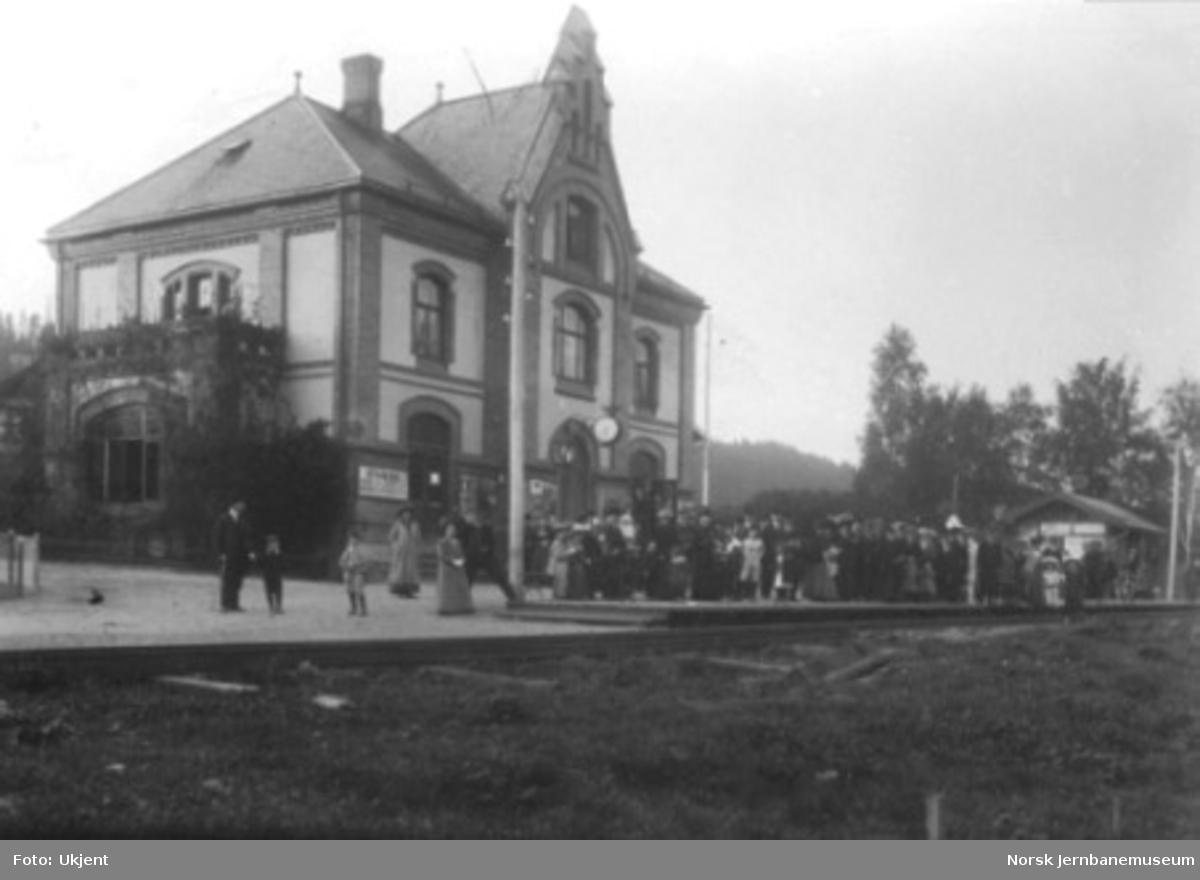 En stor forsamling på plattformen foran Stabekk stasjonsbygning