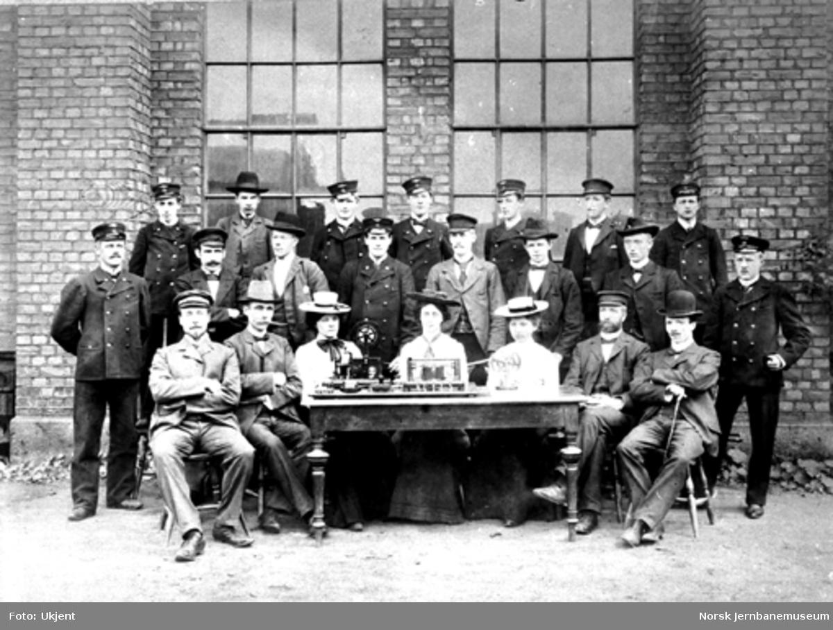Gruppebilde med 22 telegrafistelever bak et bord med telegrafiapparater