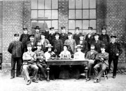 Gruppebilde med 22 telegrafistelever bak et bord med telegra