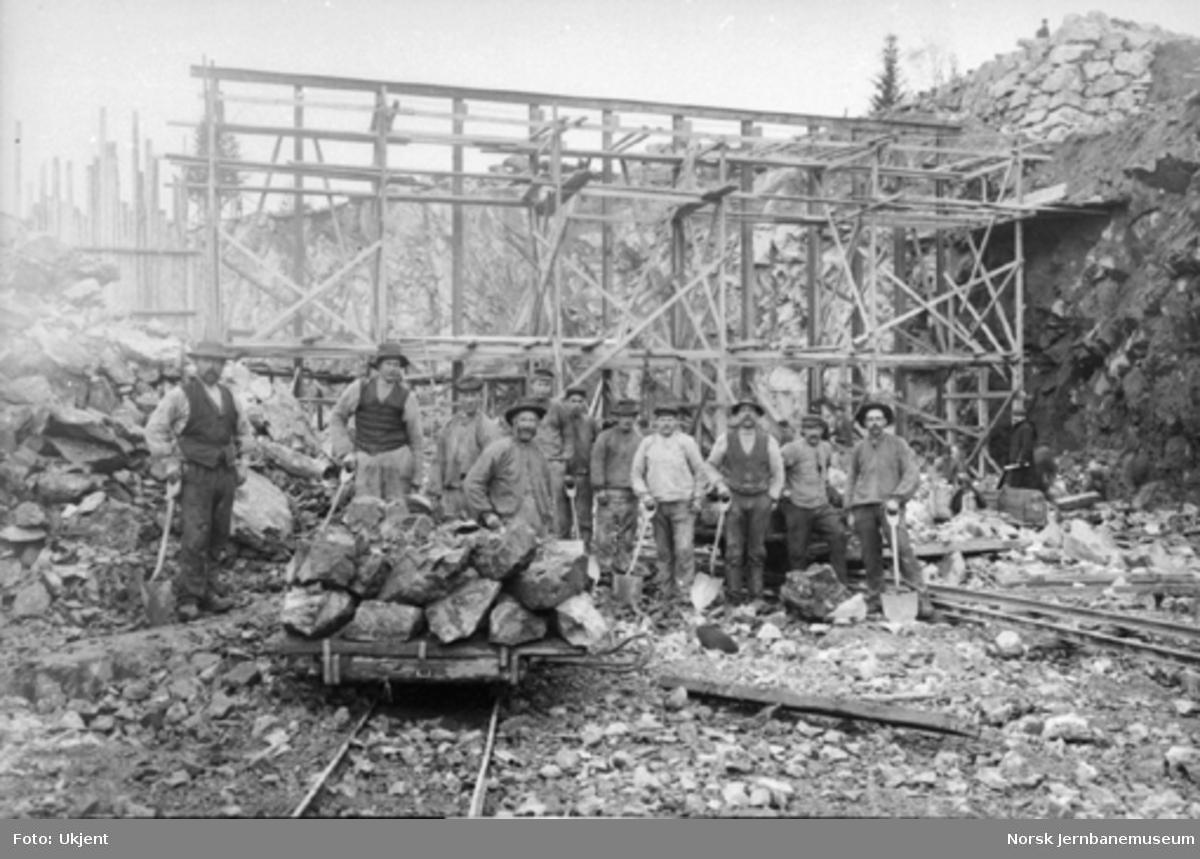 Anleggsarbeidere oppstilt bak en steintralle på ukjent anlegg, stillas i bakgrunnen