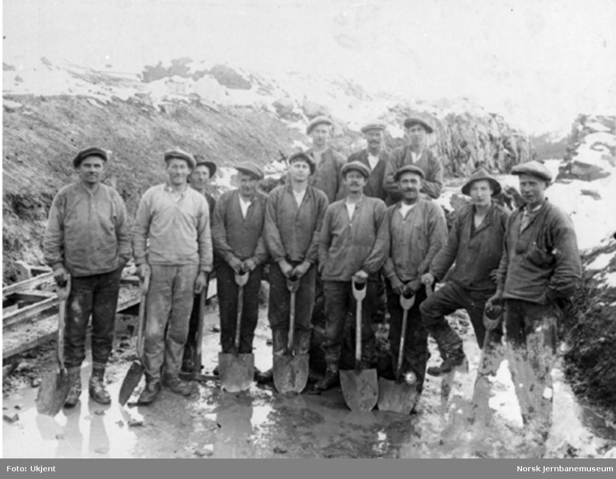 Gruppebilde av tolv anleggsarbeidere med spader