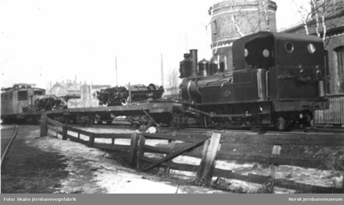 Elektrisk lokomotiv til Rjukanbanen under transport fra Skabo, trukket av et smalsporet damplokomotiv av type IV